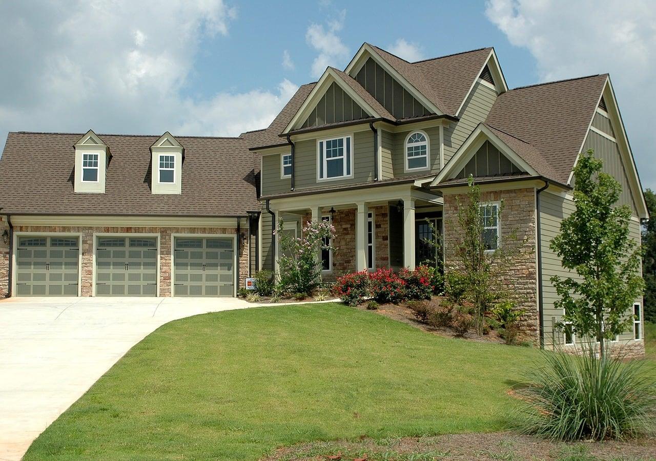 Large green suburban home with three-car garage.