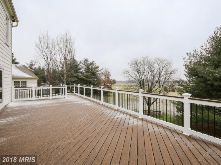 Enormous wood paneled deck with white fencing.