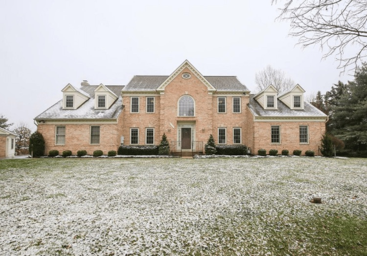 Multi-story brick home on a huge yard dusted with snow.