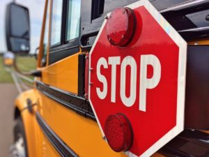 School bus with a red stop sign on the side.