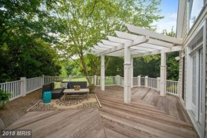 outside patio with pergola and sitting area.