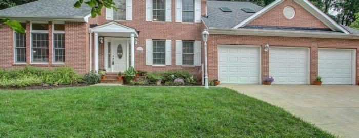 Large two-story brick home with a three-car garage.