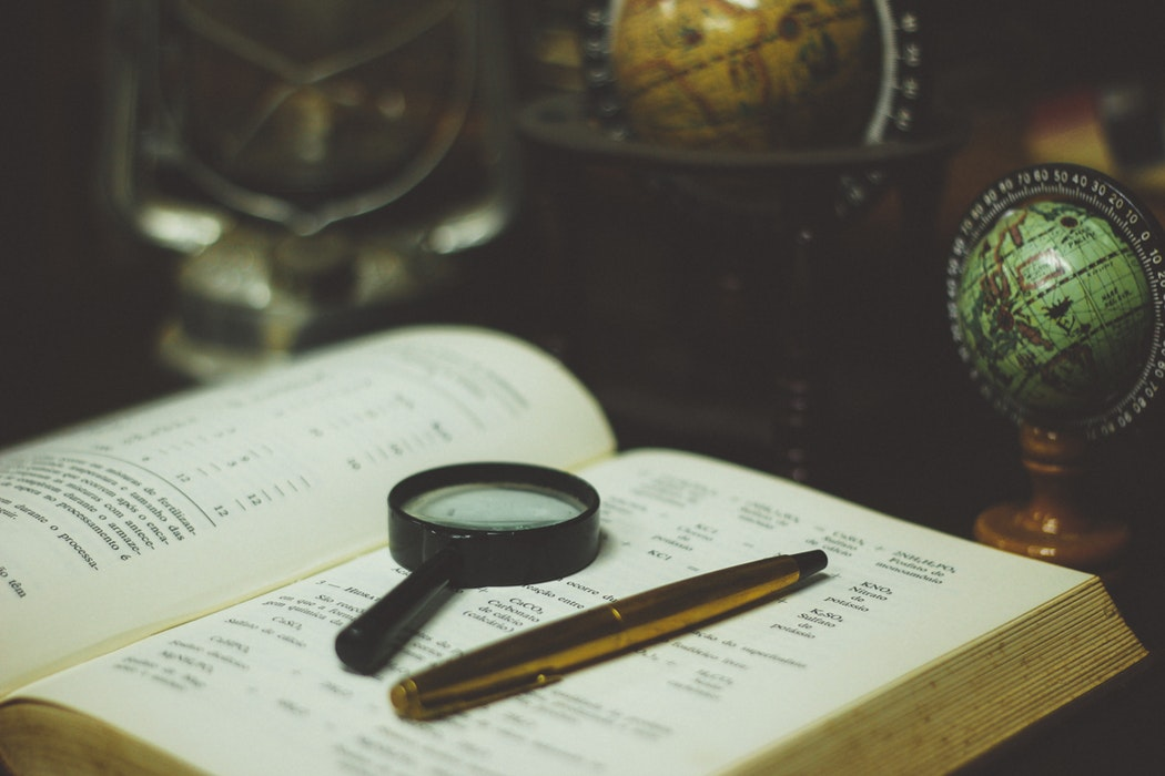 A magnifying glass and pen sitting on top of a book.